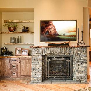 Ejemplo de salón cerrado, rural, grande, con paredes beige, suelo de madera clara, chimenea tradicional y marco de chimenea de piedra