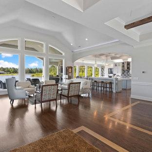 Ejemplo de salón abierto y abovedado, marinero, grande, con paredes blancas, suelo de madera oscura, chimenea tradicional, televisor colgado en la pared y suelo marrón