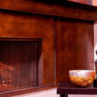 Modelo de salón abierto, contemporáneo, de tamaño medio, con paredes blancas, suelo de cemento, chimenea tradicional, marco de chimenea de metal y televisor retractable