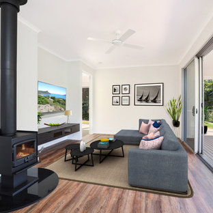 This is an example of a small modern formal open plan living room in Sunshine Coast with white walls, lino flooring, a wood burning stove, a wall mounted tv and brown floors.