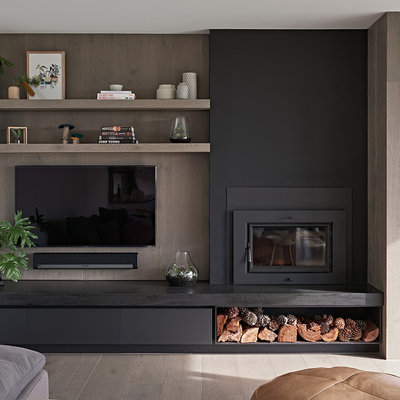 Large trendy medium tone wood floor and brown floor living room photo in Melbourne with white walls, a standard fireplace and a wall-mounted tv