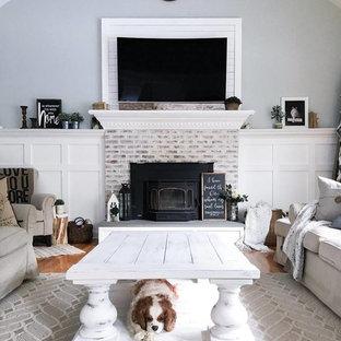 Mittelgroßes, Offenes Landhaus Wohnzimmer mit bunten Wänden, hellem Holzboden, Kamin, Kaminumrandung aus Backstein, Wand-TV und buntem Boden in Sonstige