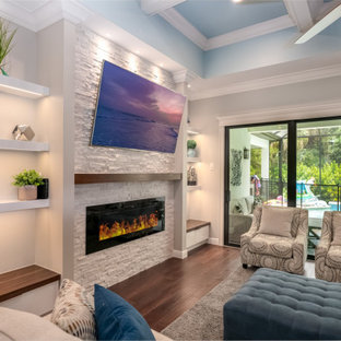 タンパのモダンスタイルのおしゃれなリビング (ベージュの壁、壁掛け型テレビ、格子天井、積石の暖炉まわり、茶色い床) の写真