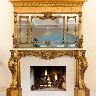 ニューヨークの中サイズのヴィクトリアン調のおしゃれなLDK (フォーマル、ベージュの壁、塗装フローリング、標準型暖炉、コンクリートの暖炉まわり、茶色い床) の写真