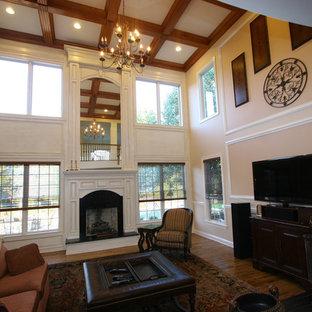 На фото: открытые гостиные комнаты среднего размера в классическом стиле с бежевыми стенами, паркетным полом среднего тона, камином, фасадом камина из дерева, отдельно стоящим ТВ и коричневым полом