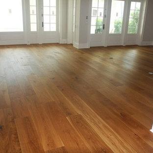Exemple d'un grand salon craftsman ouvert avec un sol en bois brun, un mur rose, aucune cheminée, aucun téléviseur et un sol marron.