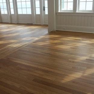 Diseño de salón abierto, de estilo americano, grande, sin chimenea y televisor, con suelo de madera en tonos medios, paredes rosas y suelo marrón