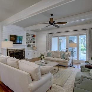 チャールストンの大きいカントリー風おしゃれなLDK (白い壁、無垢フローリング、標準型暖炉、レンガの暖炉まわり、壁掛け型テレビ) の写真