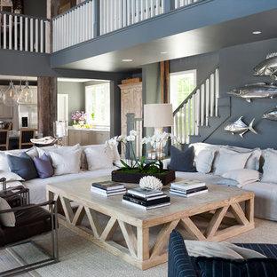 Idées déco pour un salon bord de mer ouvert avec un mur bleu et un sol en bois clair.