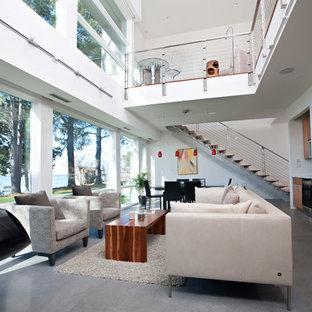 Пример оригинального дизайна: гостиная комната в современном стиле с белыми стенами, подвесным камином и бетонным полом
