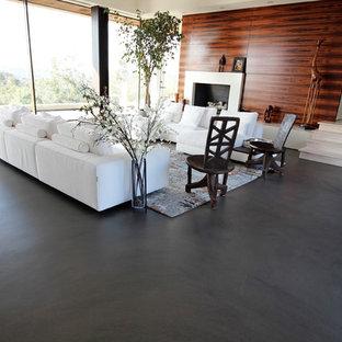 Modern inredning av ett stort allrum med öppen planlösning, med betonggolv, en standard öppen spis, en spiselkrans i trä, ett finrum, beige väggar och grått golv