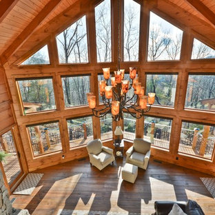 Large rustic formal open plan living room in Other with brown walls, medium hardwood flooring, a standard fireplace, a stone fireplace surround, no tv and brown floors.