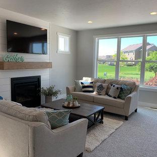 Modelo de salón machihembrado y abierto, clásico, de tamaño medio, con paredes beige, moqueta, chimenea tradicional y televisor colgado en la pared