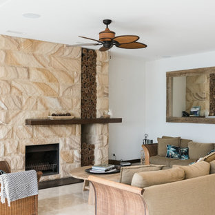 Design ideas for a tropical open concept living room in Sydney with white walls, a stone fireplace surround, no tv and beige floor.