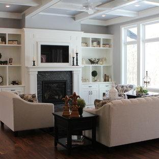 Immagine di un grande soggiorno stile americano aperto con pareti grigie, parquet scuro, camino lineare Ribbon, cornice del camino in pietra e TV nascosta