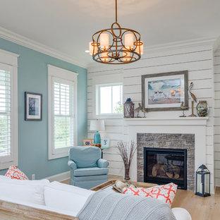 ルイビルのビーチスタイルのおしゃれなリビング (青い壁、淡色無垢フローリング、標準型暖炉、石材の暖炉まわり、テレビなし、ベージュの床) の写真