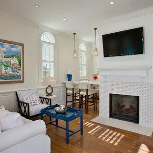オーランドの小さいビーチスタイルのおしゃれなリビング (白い壁、無垢フローリング、標準型暖炉、タイルの暖炉まわり、壁掛け型テレビ) の写真