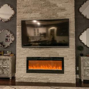 オーランドの広いラスティックスタイルのおしゃれなLDK (マルチカラーの壁、濃色無垢フローリング、横長型暖炉、石材の暖炉まわり、壁掛け型テレビ、茶色い床) の写真