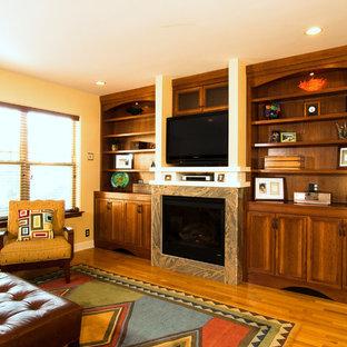 Idee per un grande soggiorno stile americano aperto con pareti gialle, parquet chiaro, camino classico, cornice del camino in pietra, pavimento giallo e parete attrezzata