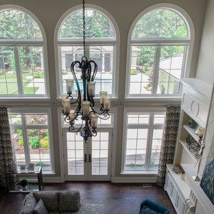 トロントの大きいトラディショナルスタイルのおしゃれな独立型リビング (フォーマル、ベージュの壁、濃色無垢フローリング、標準型暖炉、木材の暖炉まわり、テレビなし、白い床) の写真
