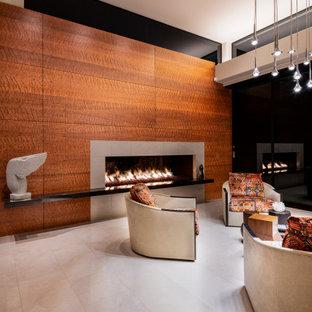 フェニックスのおしゃれなリビング (オレンジの壁、標準型暖炉、木材の暖炉まわり、白い床) の写真