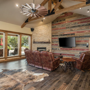 Living room - rustic formal and open concept dark wood floor and brown floor living room idea in Other with beige walls, a corner fireplace, a stone fireplace and a wall-mounted tv