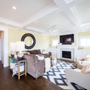 サンルイスオビスポの中サイズのビーチスタイルのおしゃれなリビング (黄色い壁、無垢フローリング、標準型暖炉、タイルの暖炉まわり、壁掛け型テレビ) の写真