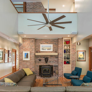 Mid-sized trendy open concept medium tone wood floor living room photo in Austin with beige walls, a wood stove, a brick fireplace and a tv stand