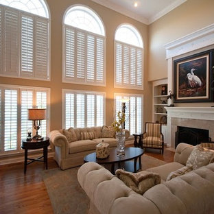 Living room - mid-sized traditional formal and enclosed medium tone wood floor and brown floor living room idea in Dallas with beige walls, a standard fireplace and no tv
