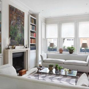 Esempio di un soggiorno contemporaneo di medie dimensioni e chiuso con libreria, pareti bianche, parquet chiaro, camino classico e cornice del camino in cemento