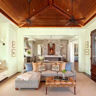 Diseño de salón abierto con paredes blancas, suelo de madera oscura, chimenea tradicional, marco de chimenea de ladrillo y televisor colgado en la pared