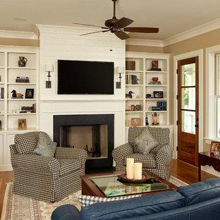 チャールストンの中サイズのトラディショナルスタイルのおしゃれな独立型リビング (標準型暖炉、壁掛け型テレビ、ベージュの壁、無垢フローリング、漆喰の暖炉まわり、ベージュの床、フォーマル) の写真