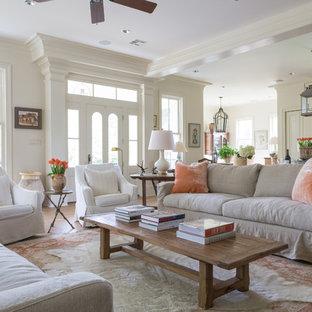 Ejemplo de salón abierto, de estilo de casa de campo, de tamaño medio, con paredes blancas, suelo de madera clara, chimenea tradicional, marco de chimenea de ladrillo, televisor colgado en la pared y suelo beige