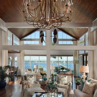 Ispirazione per un grande soggiorno tropicale aperto con pareti bianche, pavimento in legno massello medio, nessun camino e pavimento marrone