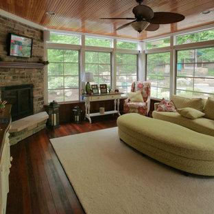 ワシントンD.C.の大きいトラディショナルスタイルのおしゃれな独立型リビング (コーナー設置型暖炉、フォーマル、茶色い壁、濃色無垢フローリング、石材の暖炉まわり、壁掛け型テレビ) の写真
