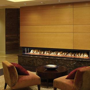 На фото: большая гостиная комната в современном стиле с бежевыми стенами, темным паркетным полом, двусторонним камином, фасадом камина из дерева и коричневым полом с
