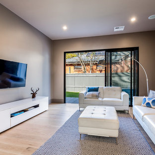 This is an example of a contemporary enclosed living room in Adelaide with brown walls, light hardwood flooring, a wall mounted tv and beige floors.