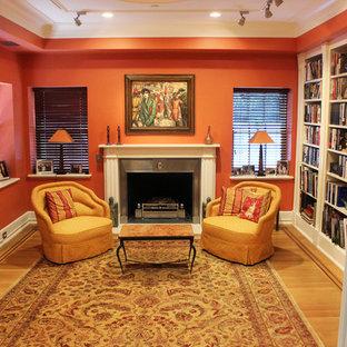 Ejemplo de biblioteca en casa cerrada, clásica, pequeña, sin televisor, con parades naranjas, suelo de madera clara, chimenea tradicional y marco de chimenea de metal