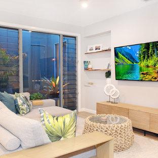 Ejemplo de salón abierto, actual, pequeño, con paredes blancas, suelo de madera clara, televisor colgado en la pared y suelo amarillo