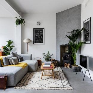 Imagen de salón abierto, nórdico, de tamaño medio, con paredes blancas, suelo de cemento, estufa de leña, televisor independiente y suelo gris