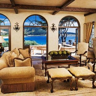 シアトルの中サイズの地中海スタイルのおしゃれなLDK (ベージュの壁、フォーマル、標準型暖炉、石材の暖炉まわり、テレビなし、ベージュの床、ライムストーンの床) の写真
