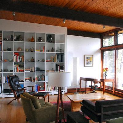Example of a minimalist medium tone wood floor living room library design in Boston