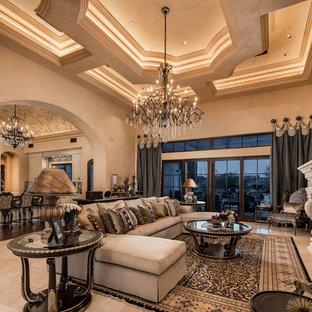Réalisation d'un très grand salon méditerranéen ouvert avec une salle de réception, un mur beige, un sol en carrelage de porcelaine, une cheminée standard, un manteau de cheminée en pierre, un téléviseur encastré et un sol beige.