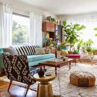 Example of an eclectic open concept medium tone wood floor and brown floor living room design in New York