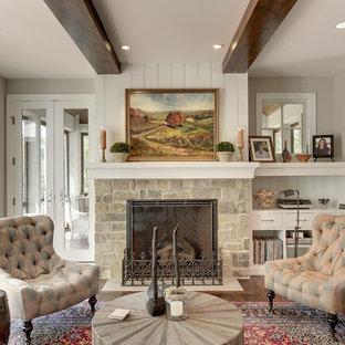 ミネアポリスのトラディショナルスタイルのおしゃれなリビング (グレーの壁、濃色無垢フローリング、標準型暖炉、石材の暖炉まわり) の写真