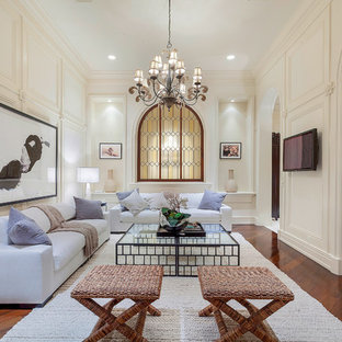Traditional living room in Miami with beige walls, medium hardwood flooring, a wall mounted tv and red floors.
