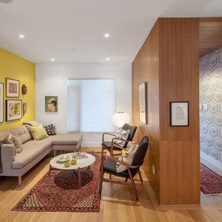 Bild på ett funkis vardagsrum, med ett finrum, gula väggar och ljust trägolv
