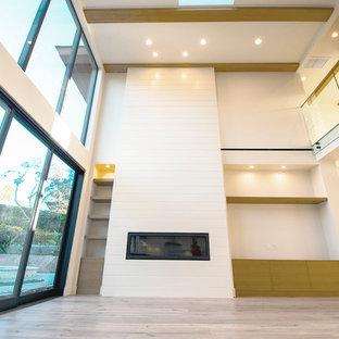 サンディエゴの大きいコンテンポラリースタイルのおしゃれなリビングロフト (白い壁、無垢フローリング、横長型暖炉、木材の暖炉まわり、埋込式メディアウォール、白い床) の写真