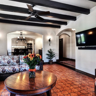 Large tuscan enclosed terra-cotta floor and brown floor living room photo in Orange County with white walls and a wall-mounted tv