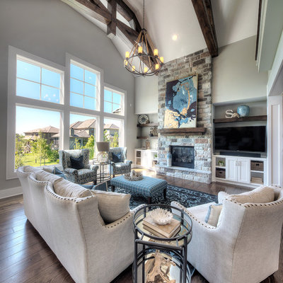 Transitional open concept dark wood floor and brown floor living room photo in Kansas City with gray walls, a standard fireplace, a stone fireplace and a wall-mounted tv